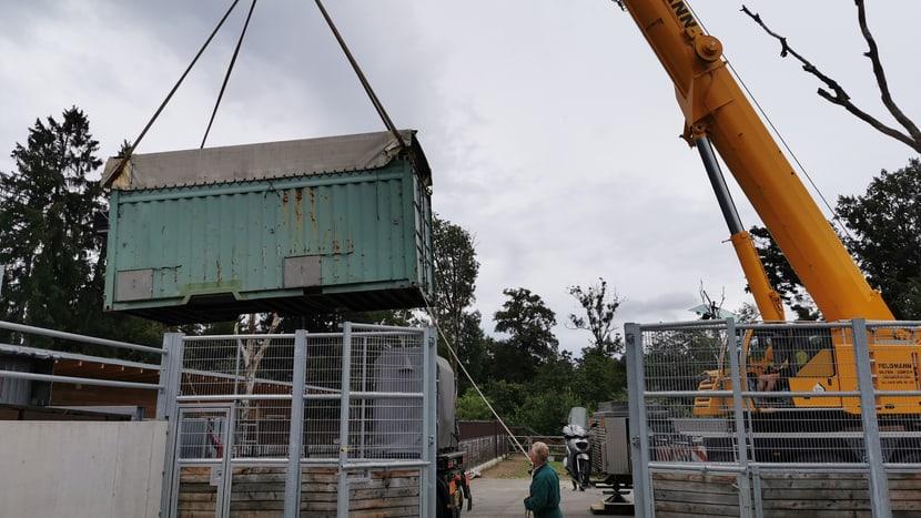 Ein Kran transportiert die Transportkiste vom Lastwagen vor den Eingang zur Quarantänebox.
